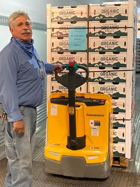 Staff member with pallet full of fresh, Colorado peaches